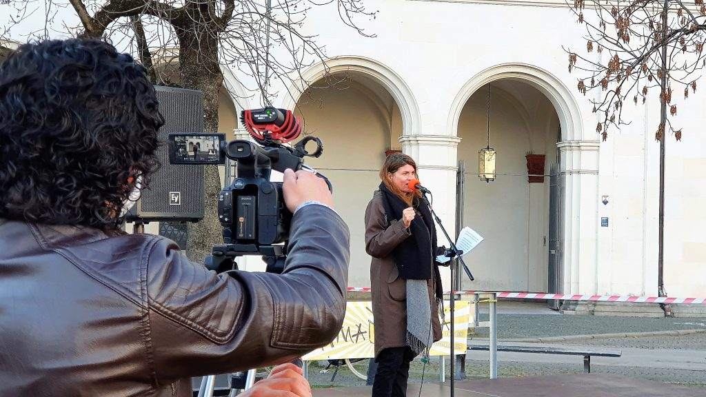 Claudia Stamm vor  dem Unigebäude am Mikrophon. Kameramann im Vordergrund filmend